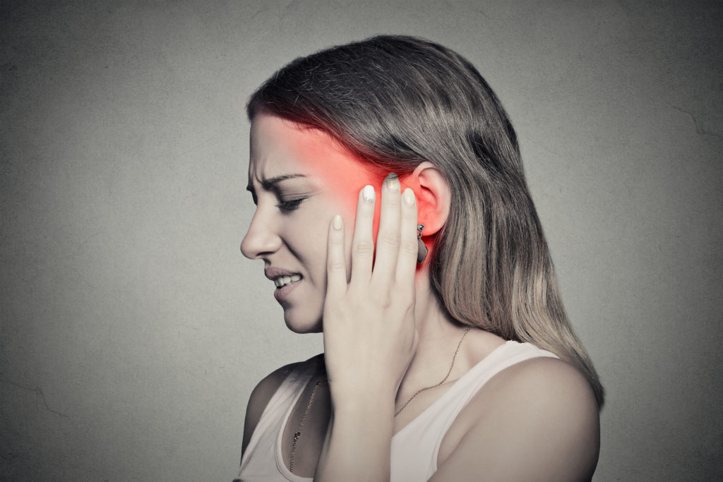 Tinnitus. Closeup up side profile sick female having ear pain touching her painful head temple isolated on gray wall background